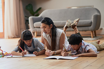 Buy stock photo Shot of a cheerful mother and her two children doing homework together while lying on the floor at home during the day