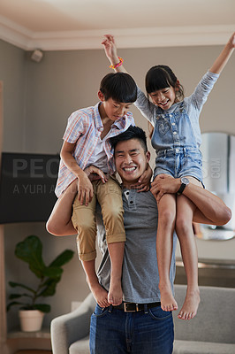 Buy stock photo Portrait of a cheerful young father holding his two children on each shoulder at home during the day
