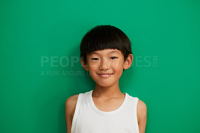Buy stock photo Studio portrait of a cheerful little boy standing against a green background during the day
