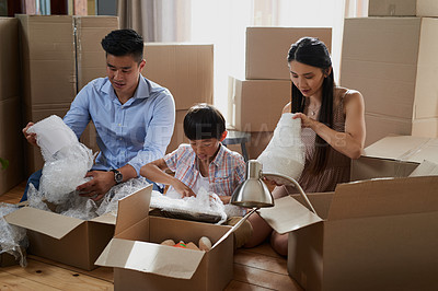 Buy stock photo Shot of a family packing boxes while moving house