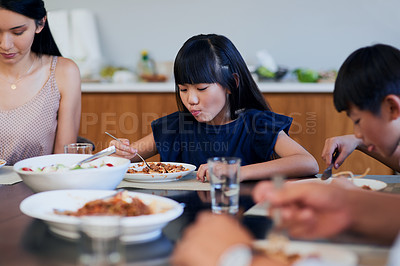 Buy stock photo Shot of two little children enjoying a meal with their mother at home
