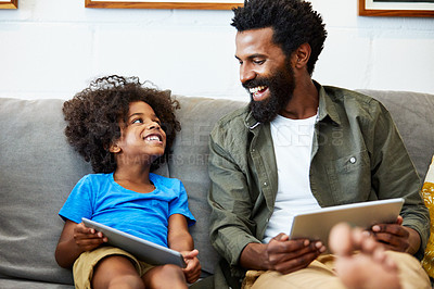 Buy stock photo Shot of a cheerful young father and son each browsing on a digital tablet while being seated on the couch at home