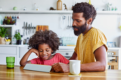 Buy stock photo Shot of a cheerful young father and son browsing on a digital tablet while having a cup of coffee in the kitchen at home