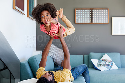 Buy stock photo Portrait of a cheerful little boy getting picked up by his dad while lying down on a couch