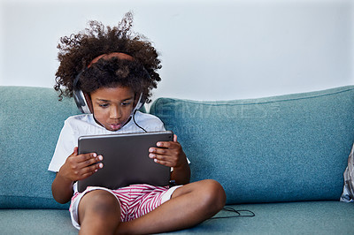 Buy stock photo Shot of a focused little boy browsing on a digital tablet and wearing headphones while relaxing on the couch at home