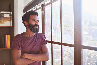 Buy stock photo Shot of a confident young man standing with his arms folded while looking through a window inside at home during the day