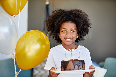 Buy stock photo Portrait of a cheerful young little boy holding a cake with balloons next to him inside at home during the day