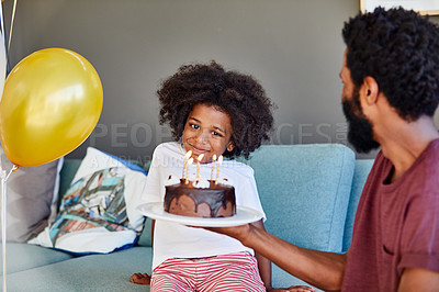 Buy stock photo Shot of a cheerful little boy receiving a birthday cake from his dad inside at home during the day