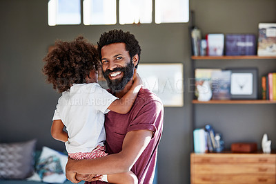 Buy stock photo Portrait of a cheerful young father holding his son while looking at the camera inside at home during the day