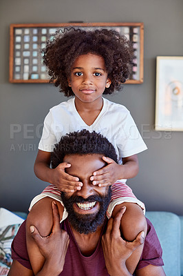 Buy stock photo Portrait of a cheerful little boy sitting on his dad's shoulders while holding his dad's eyes closed inside at home during the day