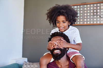 Buy stock photo Shot of a cheerful little boy sitting on his dad's shoulders while holding his dad's eyes closed inside at home during the day