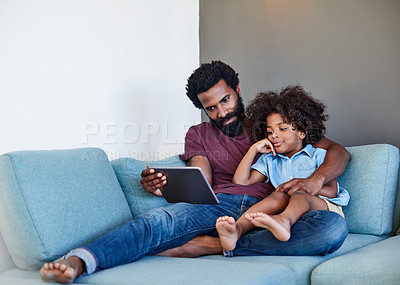 Buy stock photo Shot of a cheerful young father and son browsing on a digital tablet while relaxing on a couch at home during the day