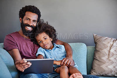 Buy stock photo Portrait of a cheerful young father and son browsing on a digital tablet while relaxing on a couch at home during the day
