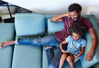 Buy stock photo High angle shot of a carefree young father and son browsing on a digital tablet while relaxing on a couch at home during the day