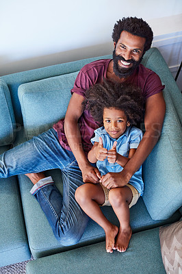Buy stock photo High angle shot of a cheerful father and son lying down and relaxing on the couch at home during the day