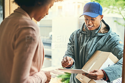 Buy stock photo Shot of a courier using a digital tablet while making a delivery to a customer