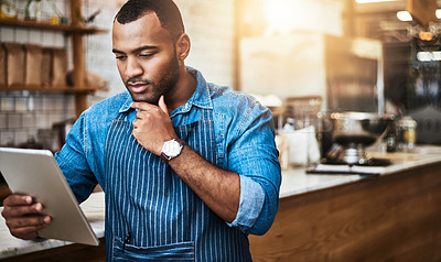 Buy stock photo Cropped shot of a handsome young man working on a tablet in his coffee shop