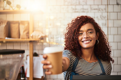Buy stock photo Portrait of a young barista holding a cup of coffee in a cafe