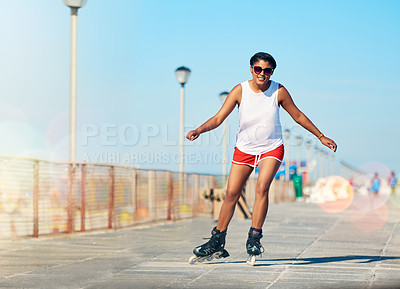 Buy stock photo Shot of an attractive young woman rollerblading on a boardwalk