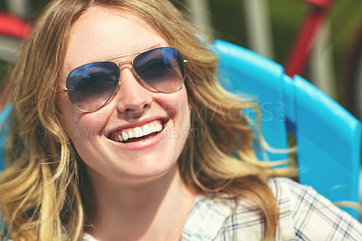 Buy stock photo Shot of an attractive young woman relaxing on a deck chair outdoors