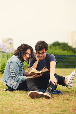 Buy stock photo Shot of a teenage couple reading a book together outdoors
