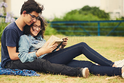 Buy stock photo Cropped shot of a teenage couple reading a book together outdoors