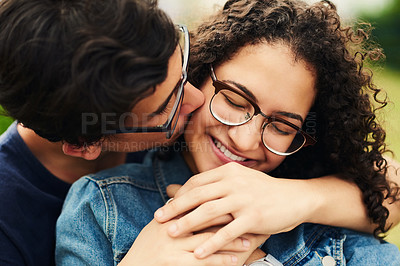 Buy stock photo Cropped shot of a teenage boy kissing his teenage girlfriend on the cheek outdoors