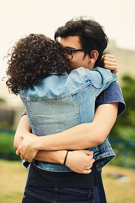 Buy stock photo Cropped shot of a teenage couple embracing each other outdoors