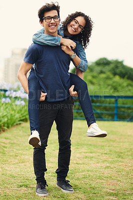 Buy stock photo Shot of a teenage girl being piggybacked by her teenage boyfriend outdoors