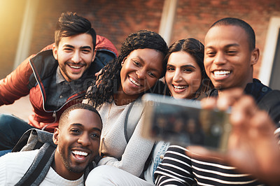 Buy stock photo Shot of a group of students taking selfies together on campus