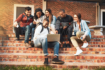 Buy stock photo Shot of a group of students using a laptop together on campus