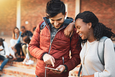 Buy stock photo Shot of a young man and woman using a mobile phone together on campus