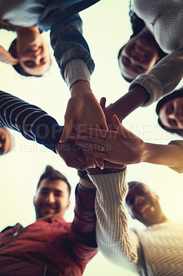 Buy stock photo Low angle shot of a group of students joining their hands in solidarity