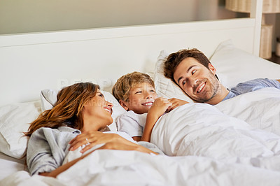 Buy stock photo Shot of a cheerful young family relaxing in bed at home during the day