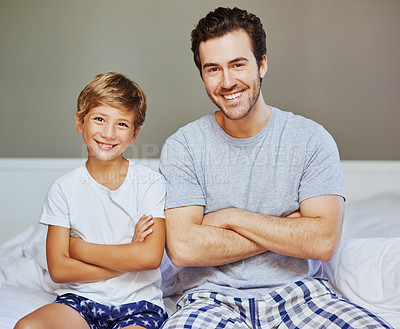 Buy stock photo Portrait of a cheerful father and son seated on a bed with arms folded while looking at the camera at home in the morning