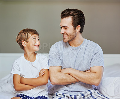 Buy stock photo Shot of a cheerful father and son seated on a bed with arms folded while looking at the camera at home in the morning