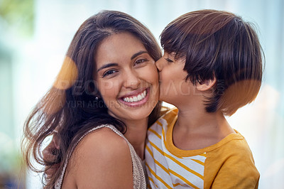 Buy stock photo Shot of an adorable little boy affectionately kissing his mother at home