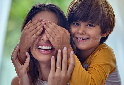 Buy stock photo Shot of an adorable little boy playfully covering his mother's eyes at home