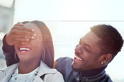 Buy stock photo Shot of a young man covering his girlfriend's eyes outdoors