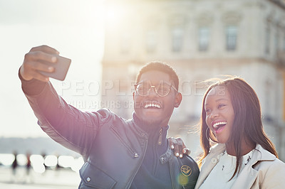 Buy stock photo Shot of an affectionate young couple taking selfies together outdoors