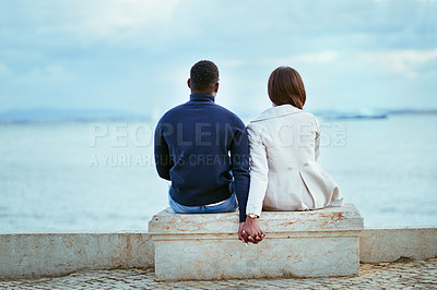 Buy stock photo Rearview shot of a young couple looking at the view of the sea outdoors