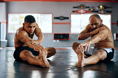 Buy stock photo Shot of two men stretching before a fight at the gym