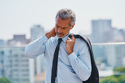 Buy stock photo Cropped shot of a mature corporate businessman experiencing body discomfort outside