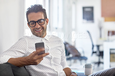 Buy stock photo Shot of a businessman using his cellphone in his office