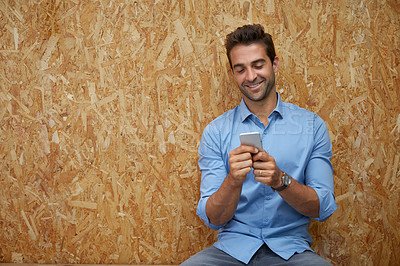 Buy stock photo Shot of a handsome young man posing against a wall