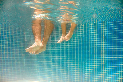 Buy stock photo Underwater shot of an unrecognizable father and son's bare feet in a swimming pool