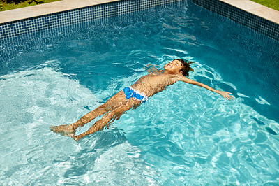 Buy stock photo Shot of a little boy floating in a swimming pool