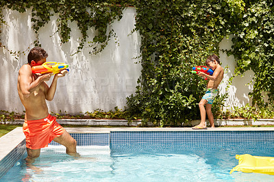 Buy stock photo Shot of a father and his son playing with water guns at the swimming pool
