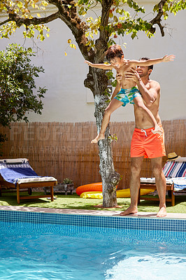Buy stock photo Shot of a father throwing his son into the swimming pool