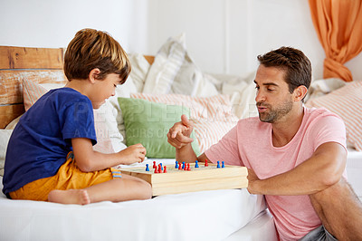 Buy stock photo Shot of a father and son playing a board game in the living room at home
